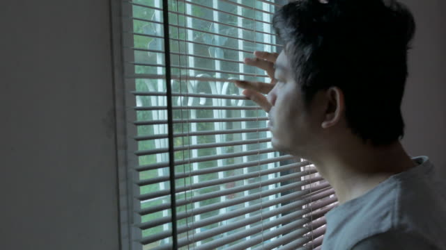 asian man wake up and looking through the window in bedroom, concept day in the life fever covid-19 quarantine - day in the life stock videos & royalty-free footage