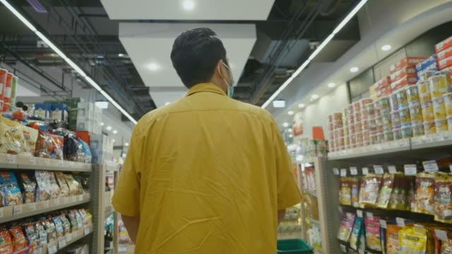 vídeos y material grabado en eventos de stock de un hombre asiático caminando en un supermercado local. - hípster urbano