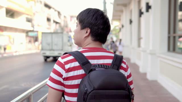 asian man walking on the street, looking around. - looking around stock videos & royalty-free footage