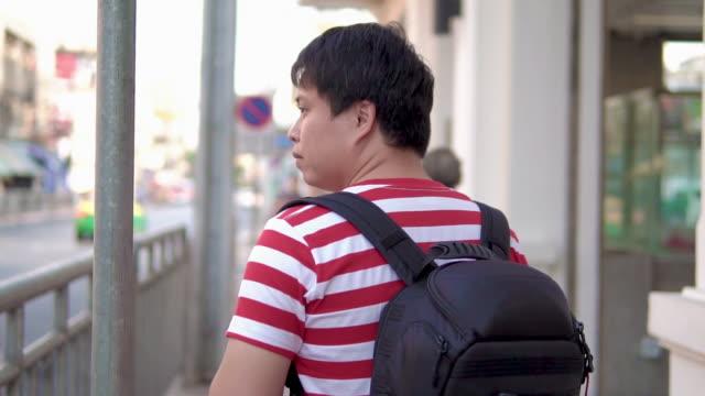vídeos y material grabado en eventos de stock de hombre asiático caminando por la calle, mirando a su alrededor. - mirar alrededor