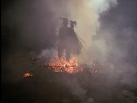 asian man walking thru burning coals + smoke / ubud, bali / indonesia - one mid adult man only stock videos & royalty-free footage