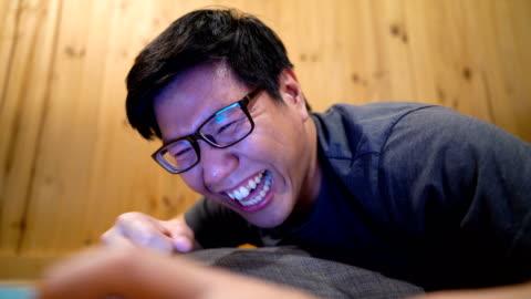 cu asiatiska man titta på en tablet pc-skärmen och skratta så hårt - koncentration bildbanksvideor och videomaterial från bakom kulisserna
