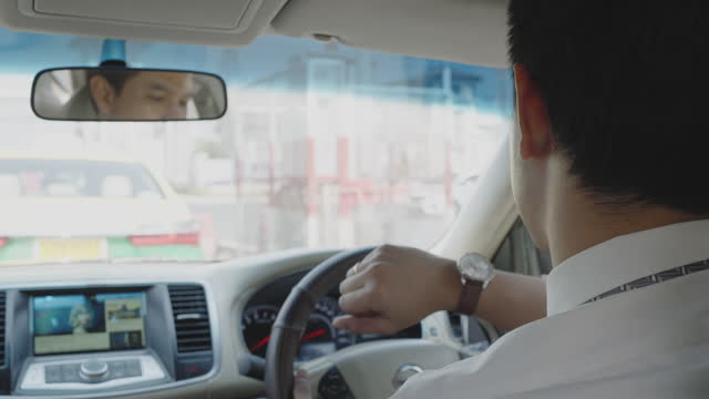 asian man watches his watch as he drives to work in the morning, late for work. traffic congestion - road signal stock videos & royalty-free footage