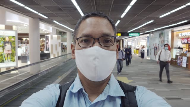 asian man wear mask at airport terminal - south east asia stock videos & royalty-free footage