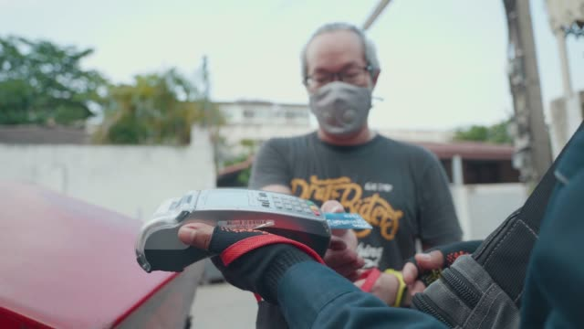 asian man wear masks waiting to receive food ordered from a delivery man riding a motorcycle pay with credit card. work from home. - casco da motociclista video stock e b–roll