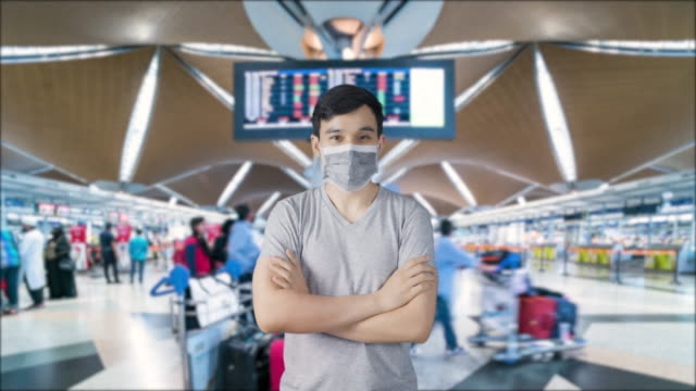 asian man wearing a mask at airport terminal (timelapse background) for prevention of novel coronavirus ncov ( covic-19) pandemic - prevention stock videos & royalty-free footage