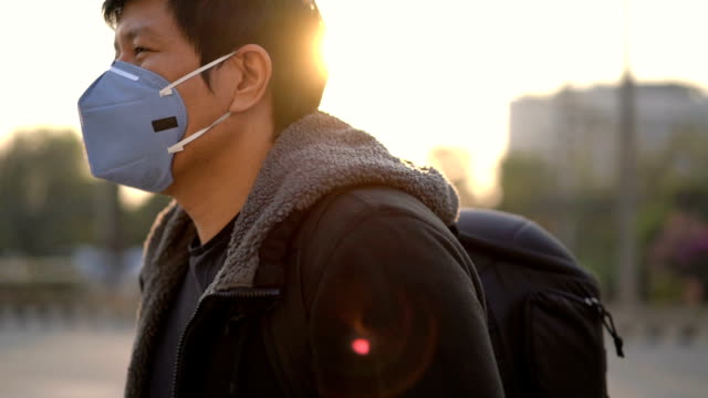 vídeos de stock e filmes b-roll de slo mo asian man wearing air pollution mask in the morning - máscara de proteção