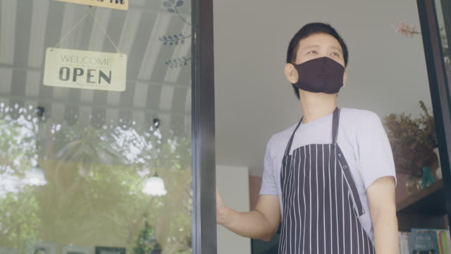 asian man wearing mask standing with open sign board on glass door in coffee shop and restaurant after coronavirus lockdown quarantine.business crisis concept.4k slow motion. - opening event stock videos & royalty-free footage
