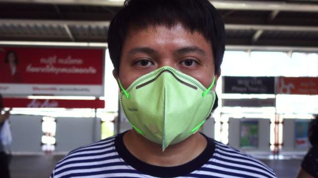 vídeos de stock e filmes b-roll de asian man wearing mouth mask against air pollution. - máscara facial