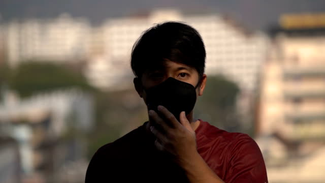 slo mo - asian man wearing pollution mask in pollution city - pollution mask stock videos and b-roll footage
