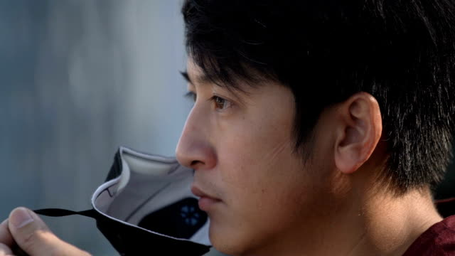 cu slomo - asian man wearing pollution mask - pollution mask stock videos and b-roll footage