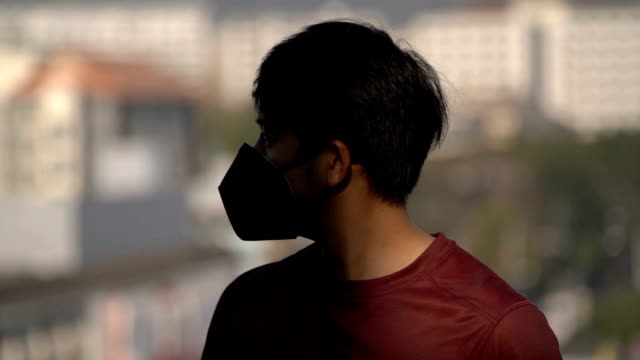 asian man wearing pollution mask with half of his face in shadow - lighting technique stock videos & royalty-free footage