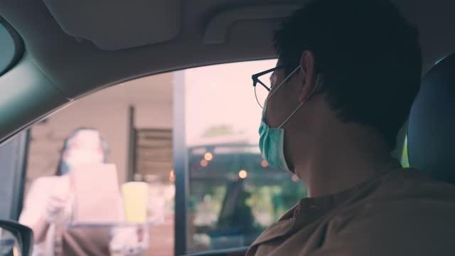 vídeos de stock, filmes e b-roll de homem asiático usando máscara protetora dirige carro e pegar comida e café de funcionário via drive thru estação de restaurante - fast food