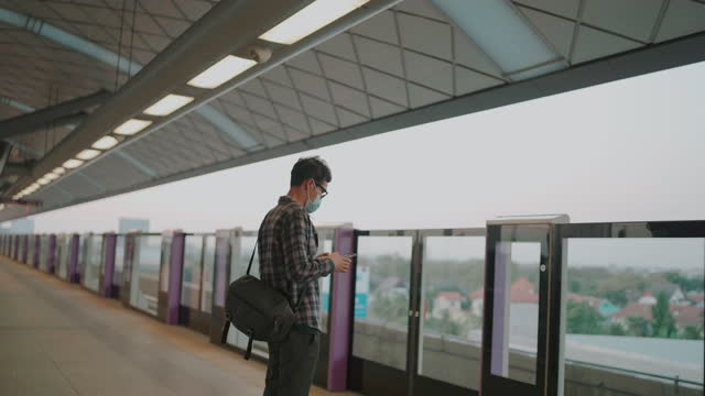 asian man wearing surgical face mask on platform waiting for train - freelance work stock videos & royalty-free footage