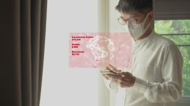 asiatisk man bär kirurgisk mask och mobil upptäckt coronavirus covid-19 - skyddsmask bildbanksvideor och videomaterial från bakom kulisserna