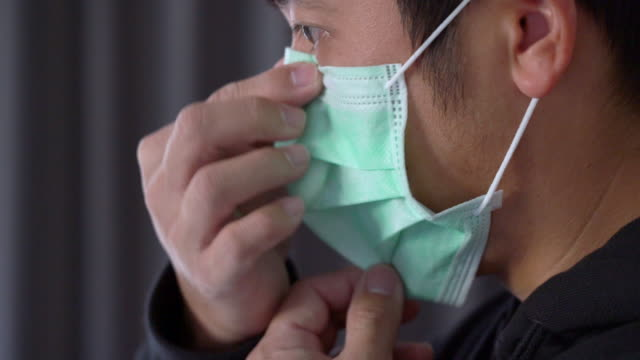 asian man wearing surgical mask to protect corona virus side view - pollution mask stock videos & royalty-free footage