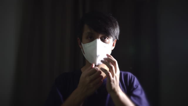 asian man wearing surgical mask to protect virus  at the dark room. - pollution mask stock videos & royalty-free footage