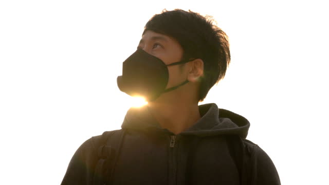 SLO MO Asian man with air pollution mask with sun light flare on white sky background