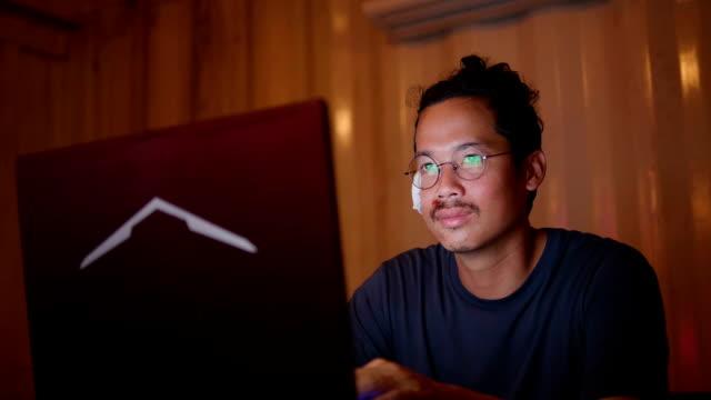 vídeos de stock e filmes b-roll de asian man with broken arm working late at night. - editorial