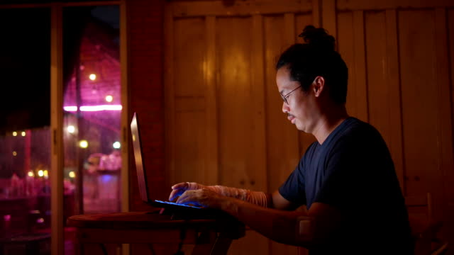 Asian man With broken arm working late at night.