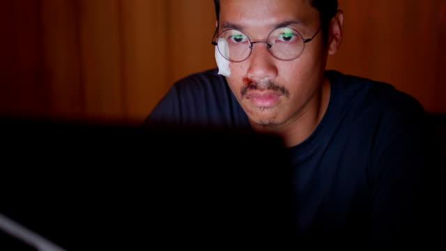 夜遅くまで働く壊れた腕を持つアジア人。 - 編集者点の映像素材/bロール