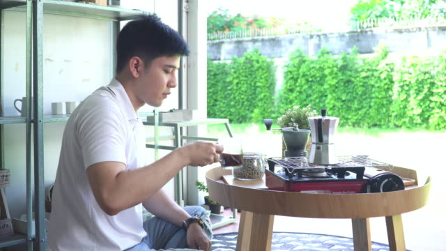 asian man with casual clothing sitting on  balcony, making coffee with feeling positive emotion and happiness, enjoyment, looking garden in home, drinking coffee for resting and taking a break as aromatherapy and ritual - one mid adult man only stock videos & royalty-free footage