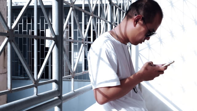 Asian Man With Eyeglasses Using Smartphone