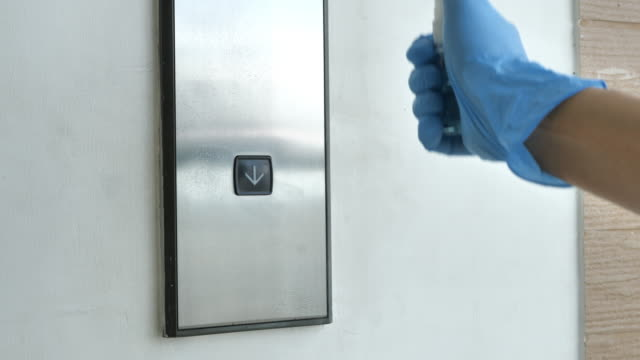 asian man with glove wiping down the elevator button - claustrophobia stock videos & royalty-free footage