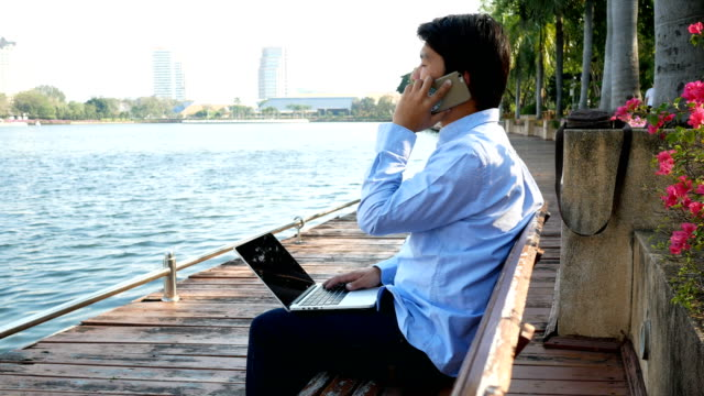 Asian man with his mobile phone and laptop at outdoors