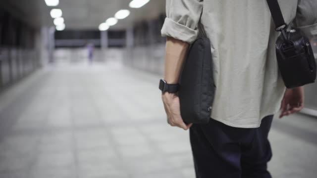 vídeos de stock, filmes e b-roll de homem asiático com saco de mensageiro usando celular e ir embora quando a hora é de volta para casa à noite - plano americano