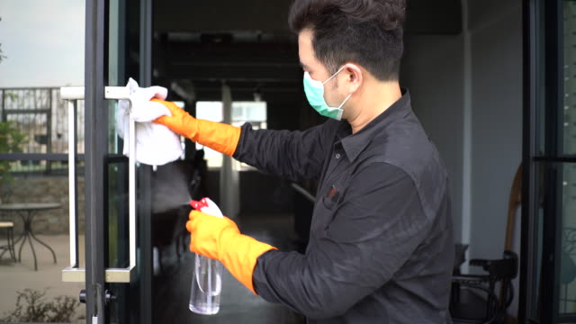 asian man with protective mask and glove disinfecting black aluminium and glass door - washing up glove stock videos & royalty-free footage