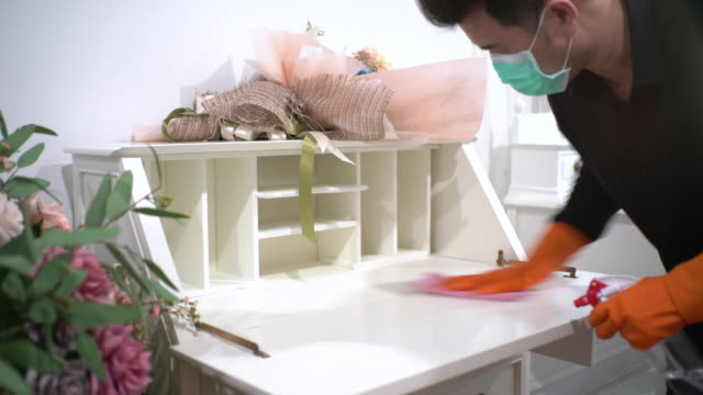 asian man with protective mask and glove disinfecting classical writing desk - washing up glove stock videos & royalty-free footage