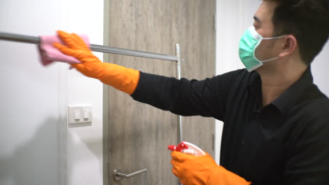asian man with protective mask and glove disinfecting cloth hanging rod - washing up glove stock videos & royalty-free footage
