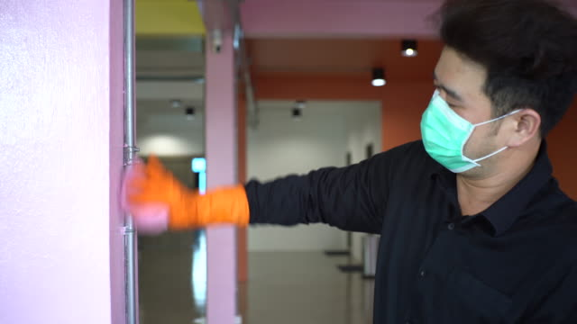 asian man with protective mask and glove disinfecting electric pipe on the wall - washing up glove stock videos & royalty-free footage