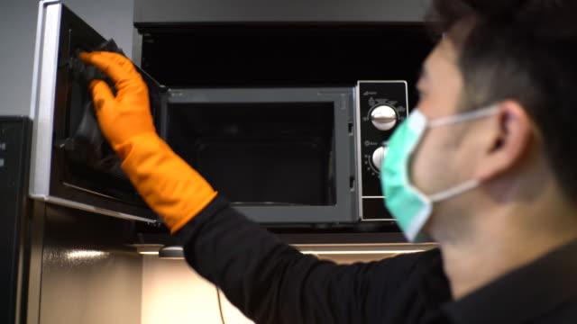 asian man with protective mask and glove disinfecting microwave - 電子レンジ点の映像素材/bロール