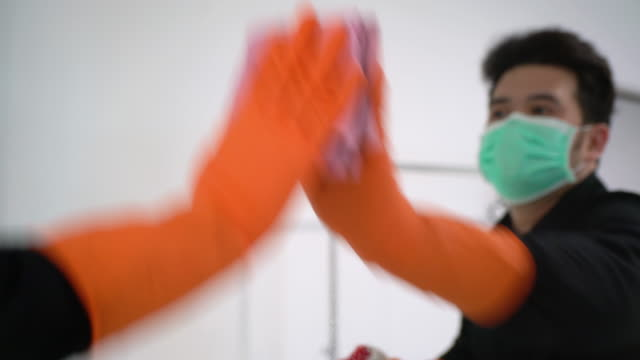 asian man with protective mask and glove disinfecting mirror surface - washing up glove stock videos & royalty-free footage