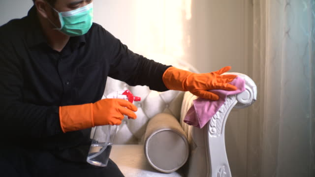 asian man with protective mask and glove disinfecting white sofa - washing up glove stock videos & royalty-free footage