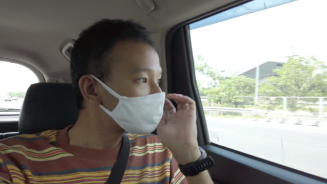 4k asian man with protective medical mask on car. hand on chin . - hand on chin stock videos & royalty-free footage
