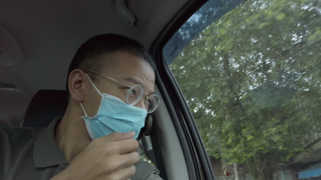 4k asian man with protective medical mask sneezing on car - asian man coughing stock videos & royalty-free footage