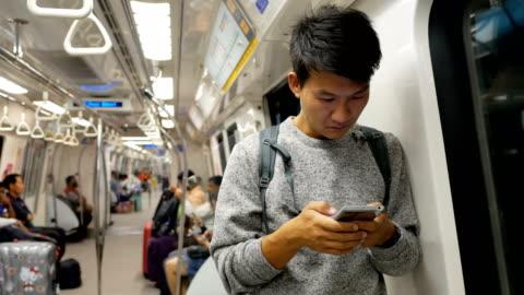 vídeos y material grabado en eventos de stock de hombre asiático con smartphone en el metro - metro transporte