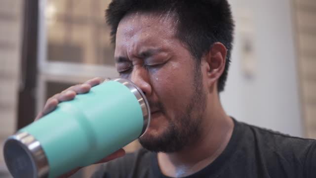 vídeos de stock, filmes e b-roll de homem asiático com suor no rosto bebendo água após exercício em casa - frio