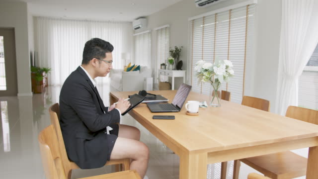 asian man work meeting and taking conference call comfortably at home during quarantine. - pyjamas stock videos & royalty-free footage