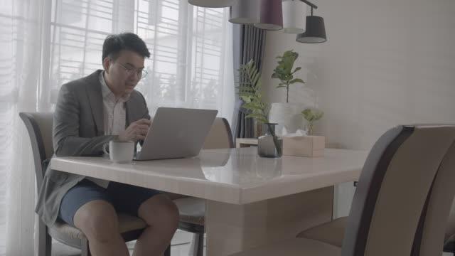 asiatischer mann arbeitet von zu hause aus in einem behelfsmäßigen büro auf esstisch zu hause - chaos stock-videos und b-roll-filmmaterial