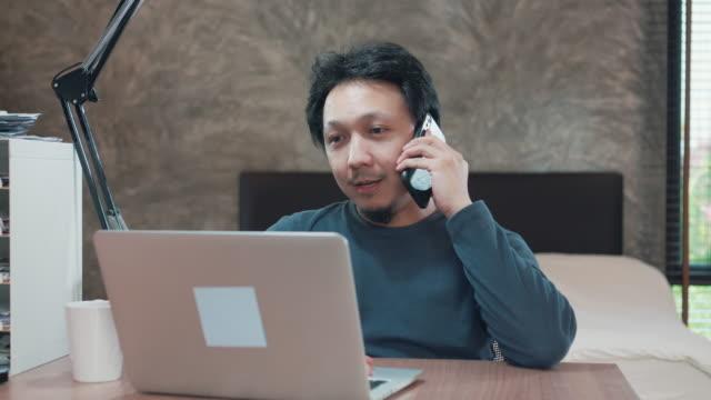 ラップトップと携帯電話を使用して自宅から働くアジアの男 - 30代点の映像素材/bロール