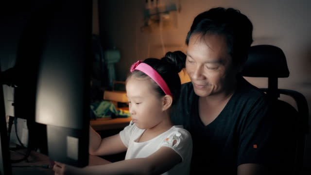 asian man working from home with his daughter enjoying a smartphone. - single father stock videos & royalty-free footage