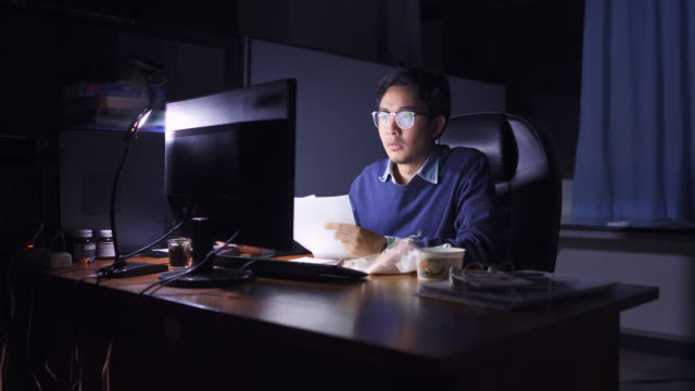 asian man working late and eating in offfice at night. overtime concept - front view stock videos & royalty-free footage