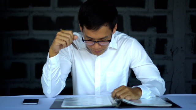 stockvideo's en b-roll-footage met aziatische man aan het werk op grafiek alvorens te kijken naar de raad van bestuur - graph