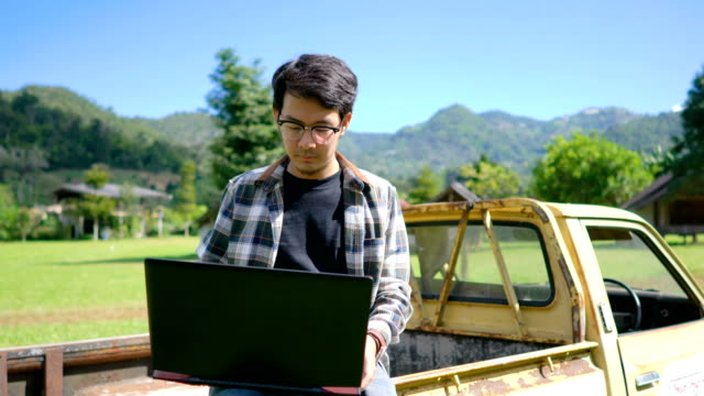 asian man working on laptop outdoors - trattore video stock e b–roll