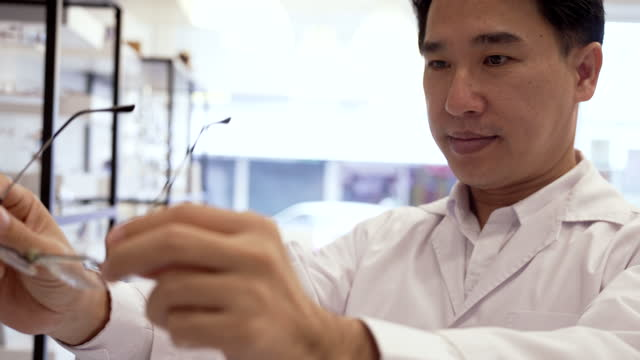 asian man working optical store. - lens optical instrument stock videos & royalty-free footage