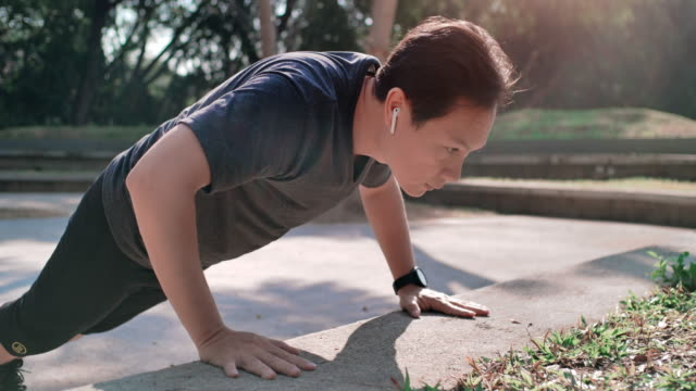 asian man working out by doing push up exercises and listening to music - push ups stock videos & royalty-free footage